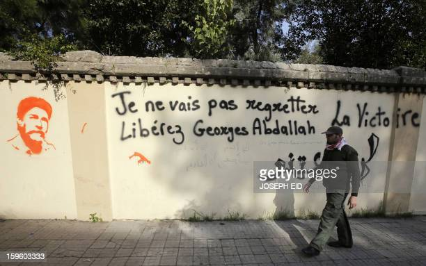 An activist walks past a graffiti of Lebanese militant Georges Ibrahim Abdallah sprayed on a wall opposite to the French embassy in Beirut to protest...