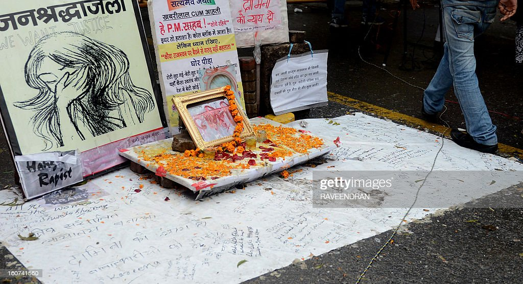 An activist walks past a memorial for the murdered gang rape victim at Jantar Mantar in New Delhi on February 5, 2013. The companion of an Indian medical student who died after being gang-raped on a bus in New Delhi was to begin giving evidence on Tuesday in the trial of five adults accused of her murder, his father said.
