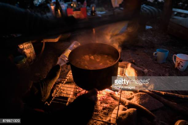 An activist warms their feet while cooking a stew for a cold Autumn evening Starting in 2012 the Hambach Forest occupation settlements have slowed...