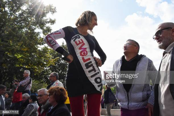 An activist wearing a dress writing on it revolution take part in a protest during the nationwide strike called by various French unions against...