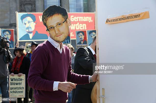An activist wearing a mask of fugitive US intelligence leaker Edward Snowden tries to get past a door reading 'Investigation Committee' during a...