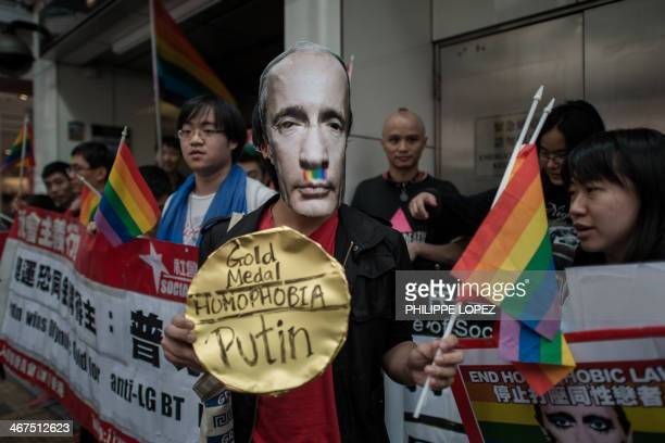An activist wearing a mask of Russian President Vladimir Putin joins protesters against Russia's antigay legislation on the day of the opening...