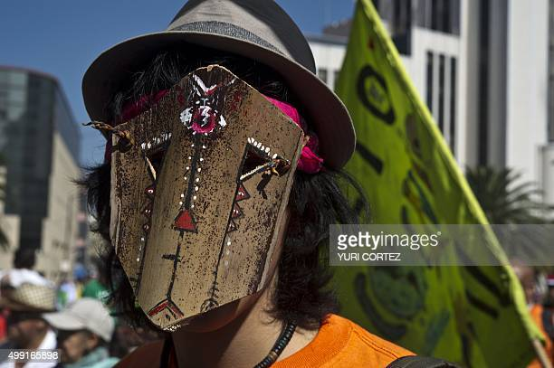 An activist wears a mask during the Global Climate March in Mexico City on November 29 on the eve of the UN conference on climate change COP 21 to...