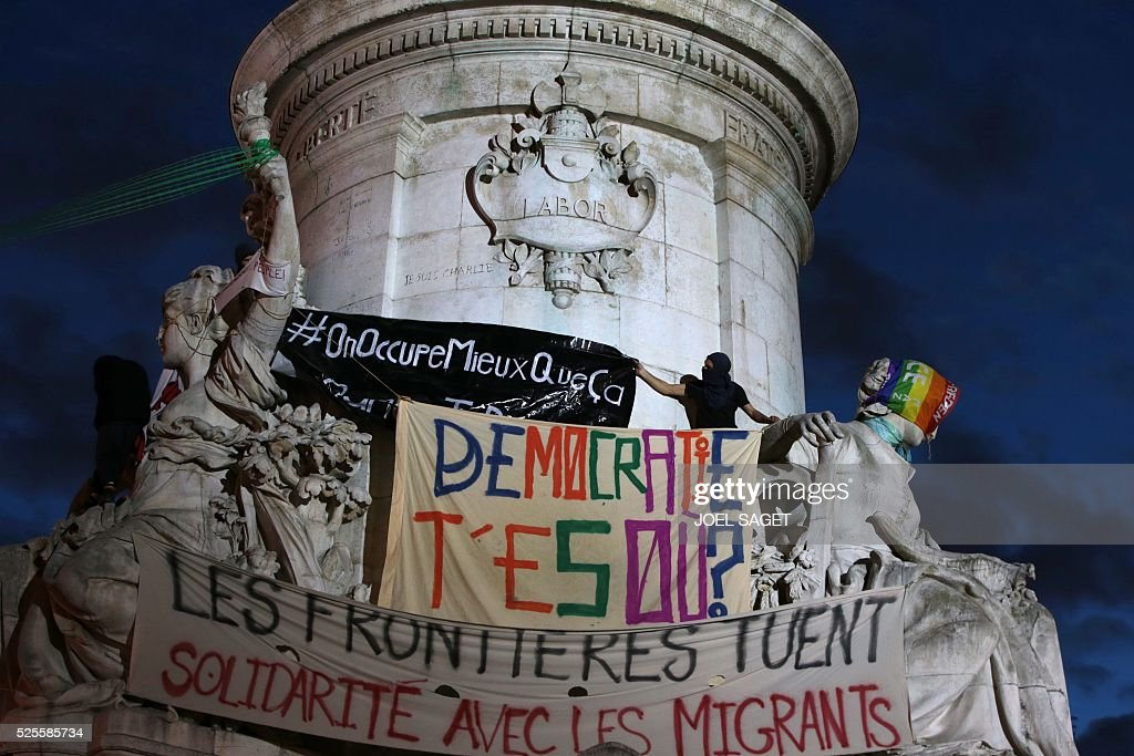 An activist who climbed onto the monument at the center of the Place de la republique, unfolds a banner reading 'We occupy better than this' during the Nuit Debout, or 'Up All Night' movement on April 28, 2016 in Paris. The 'Nuit Debout' demonstrations began on March 31 in opposition to the government's proposed labour reforms. Other banners read 'Where are you Democracy ?', 'Borders are killing' and 'Solidarity with the migrants'.