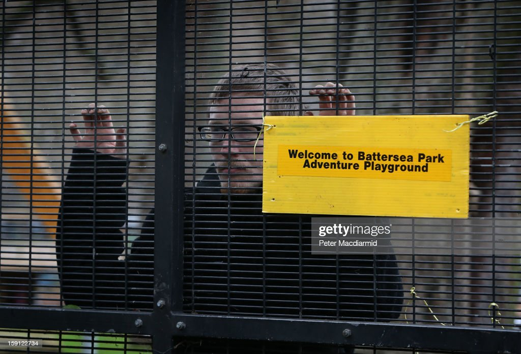 An activist, who is inside the now locked Battersea Park adventure playground, looks out from the main gate on January 8, 2013 in London, England. Activists and local residents oppose local authority plans to demolish the adventure playground, which has been mostly used by teenagers, and replace it with facilities for younger children who will need less supervision.