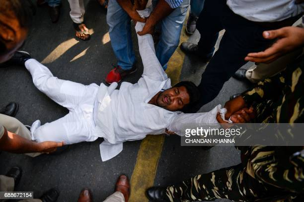An activist with the Indian Youth Congress is pulled away by police during a protest following the completion of three years of National Democratic...