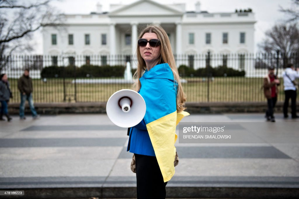 An activist wrapped in Ukraine's flag stands outside the White House during an anti-Putin protest March 12, 2014 in Washington, DC ahead of meetings between US President Barack Obama and Ukrainian Prime Minister Arseniy Yatsenyuk. Leading world powers in the Group of Seven warned Wednesday against Russia's 'annexation' of Crimea as the Ukrainian premier prepared to seek President Obama's help against the Kremlin's expansionist threat. AFP PHOTO/Brendan SMIALOWSKI