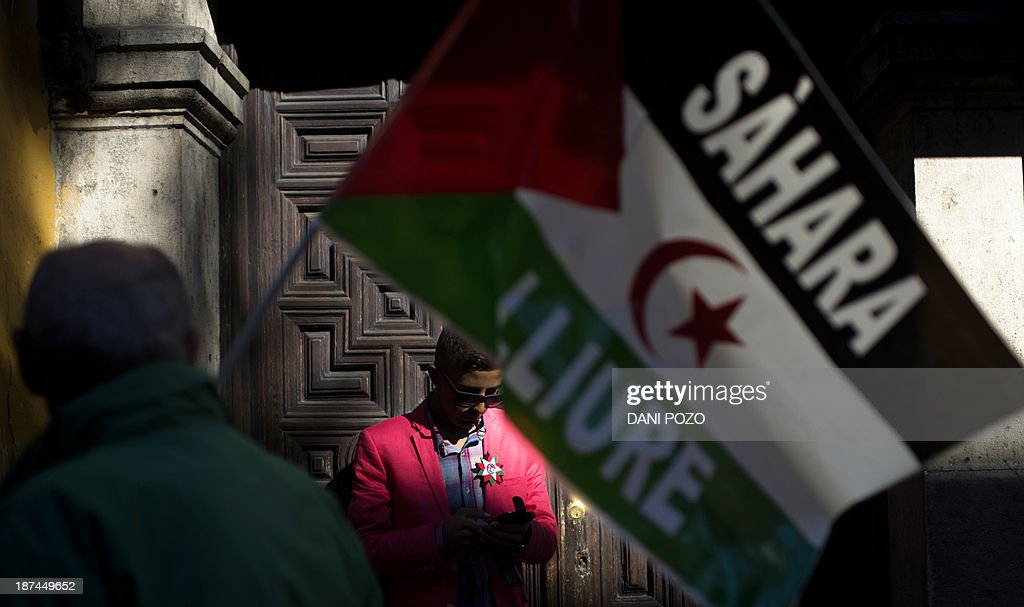 An activists for the independence of the Western Sahara passes in front of a man in a pink jacket during an annual protest organised by the state coordinator of associations of solidarity with the Sahara in Madrid on November 9, 2013 marking the 38th anniversary of the tripartite Madrid agreements demonstrators deem illegal. The Western Sahara is a territory bordered by Morocco and Algeria and disputed by Spain and Morocco who both claiming sovereignty.