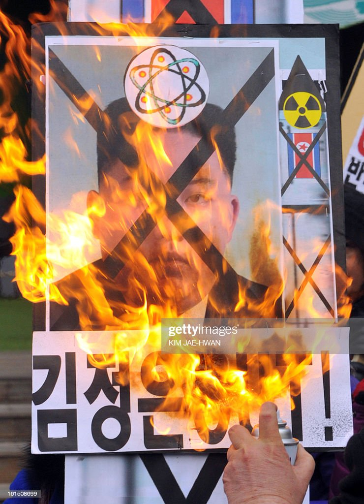 An activists from an anti-North Korea civic group burns a placard of North Korean leader Kim Jong Un during a protest in Seoul on February 12, 2013. North Korea staged its most powerful nuclear test yet, claiming a breakthrough with a 'miniaturised' device in a striking act of defiance to global powers including its sole patron China..