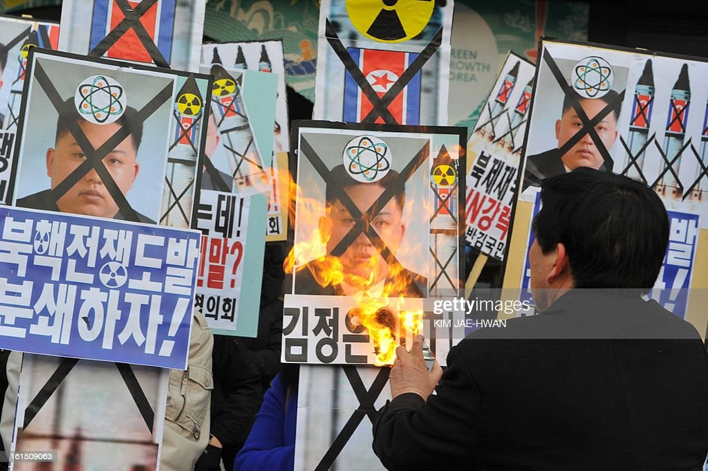 An activists from an anti-North Korea civic group burns a placard of North Korean leader Kim Jong Un during a protest agains North Korean nuclear test in Seoul on February 12, 2013.North Korea staged its most powerful nuclear test yet, claiming a breakthrough with a 'miniaturised' device in a striking act of defiance to global powers including its sole patron China.
