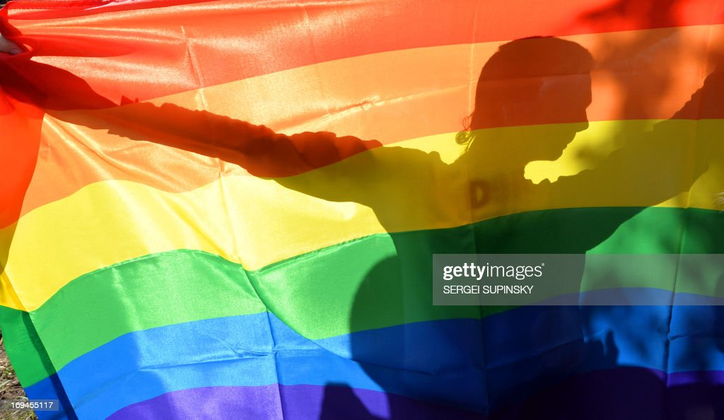 An activist's silhouette is seen through a rainbow flag during a Gay Parade in Kiev on May 25 2013 Around a hundred gay rights activists marched in...