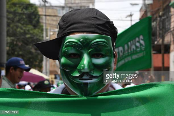 An activisy wearing a Guy Fawkes mask takes part in a march during May Day celebrations in Tegucigalpa on May 1 2017 / AFP PHOTO / ORLANDO SIERRA