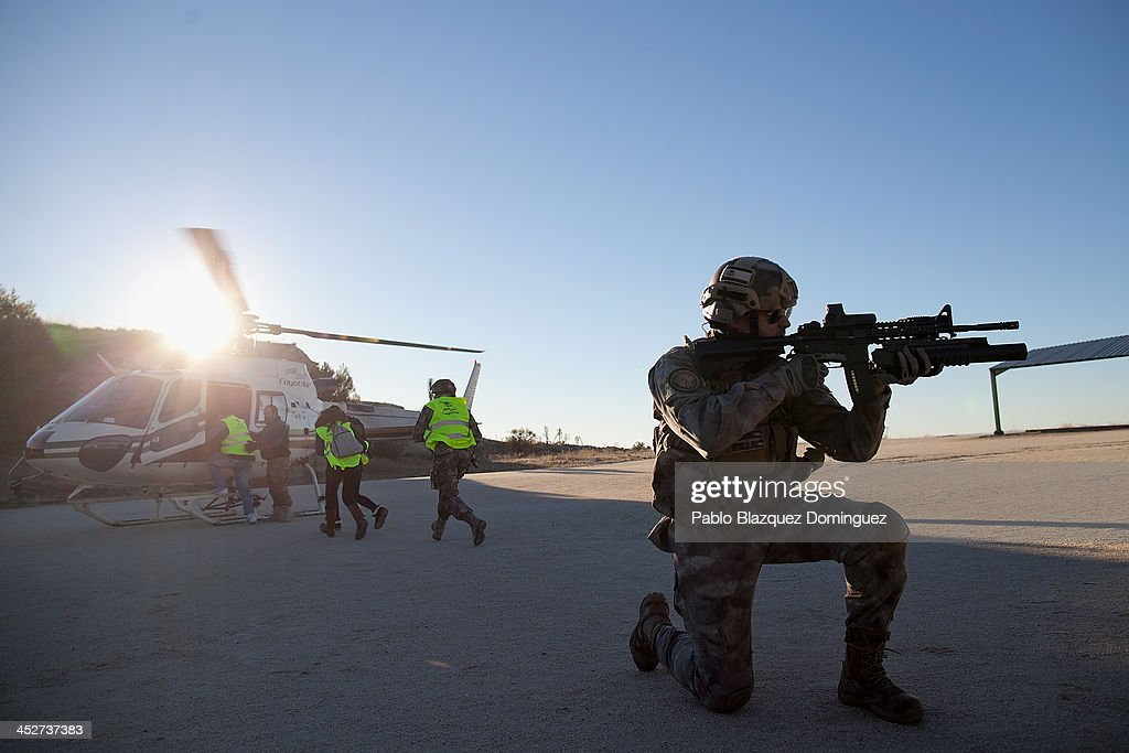 An actor dressed as a soldier protects winners as they board the helicopter during Zombie Survival contest on December 1, 2013 in Alameda de la Sagra, near Toledo, Spain. 'Zombie Survival' is a contest taking place all around Alameda de la Sagra where participants have to avoid getting touched by Zombies and find all clues to survive. The winners will leave the village by helicopter.