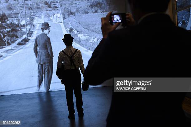 An actor dressed as Charile Chaplin stands in front of a film projection during a press visit of Chaplin's World Museum in CorsiersurVevey western...