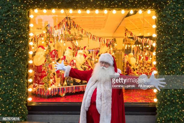 An actor dressed as Father Christmas beside a Christmas window display themed as With Love From which is a celebration of the cities Selfridges calls...