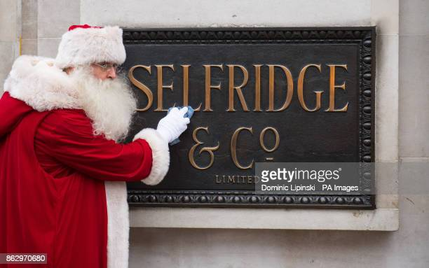 An actor dressed as Father Christmas polishes the sign at Selfridges as the store unveils its Christmas window displays themed as With Love From...