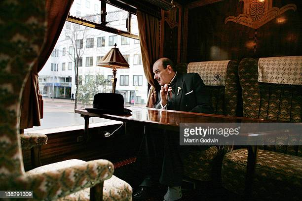 An actor dressed as Hercule Poirot sitting in an original first class parlour car 'Zena' from the Orient Express train built in 1928 and decorated in...