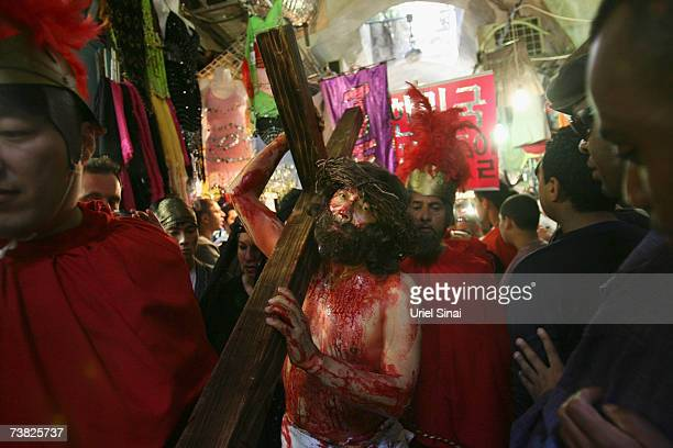 An actor dressed as Jesus Christ carries a cross as he reenacts the crucifixion after visiting the stations of the Cross during the Good Friday...