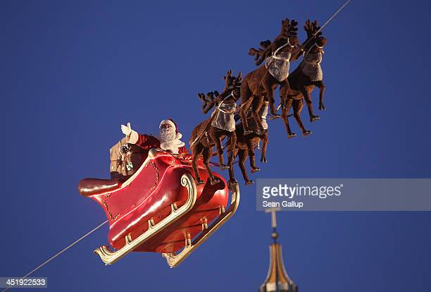 An actor dressed as Santa Claus waves from a suspended sleigh over a Christmas market as the Dom cathedral stands behind on November 25 2013 in...