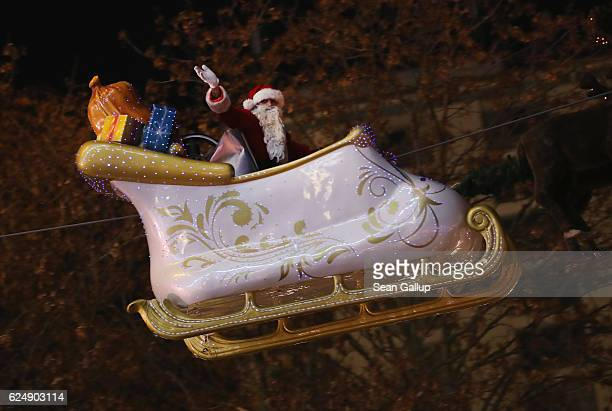 An actor dressed as Santa Claus waves to onlookers from his sled suspended above the annual Christmas market at Alexanderplatz on the market's...