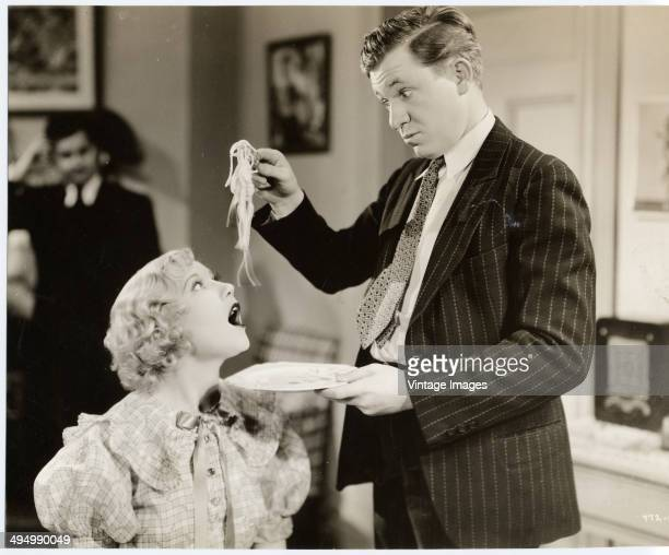 An actor feeds a plate of spaghetti to an actress in a scene from a film circa 1935