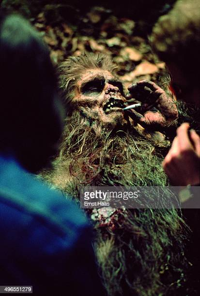 An actor in makeup takes a break during the filming of 'Quest for Fire' 1980