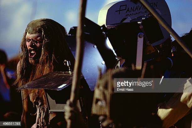 An actor possibly Everett McGill performing facial exercises next to a Panavision Panaflex camera during the filming of 'Quest for Fire' 1980
