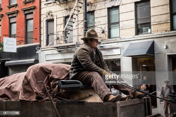 An actor rides a top a horsedrawn cart on a set for a television show currently being filmed on November 6 2013 in the Lower East Side neighborhood...