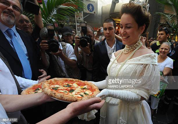 An actress dressed like Queen Margherita of Savoy is presented a pizza named after her during a ceremony to celebrate the 120th anniversary of the...
