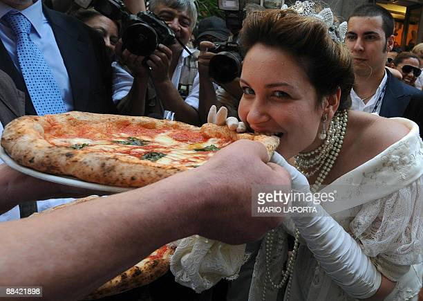 An actress dressed like Queen Margherita of Savoy tastes a pizza named after her during a ceremony to celebrate the 120th anniversary of the pizza...