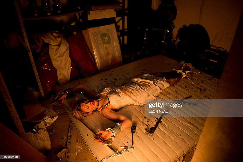 An actress is chained to a dirty mattress in the cellar beneath a film set pop-up experience in east London on January 17, 2013. The event was held to promote the release of a new horror film 'The Helpers'.