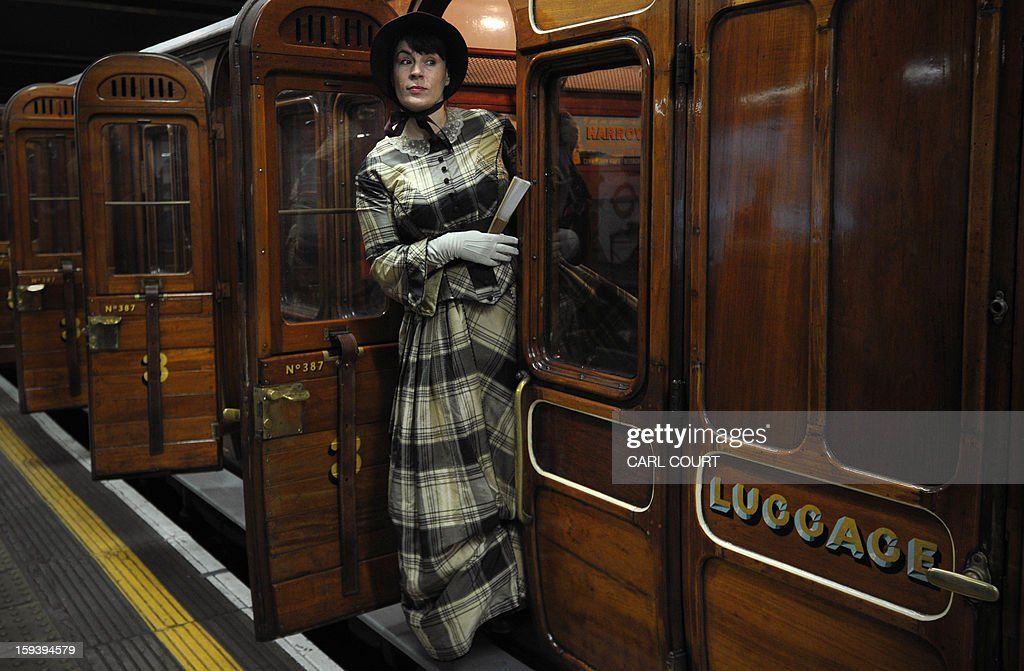 An actress wearing period costume poses for photographers next to a steam train which used to carry passengers in the 19th century as it arrived at Moorgate Underground Station in central London on January 13, 2013, to mark 150 years since the first London underground journey. AFP PHOTO / CARL COURT