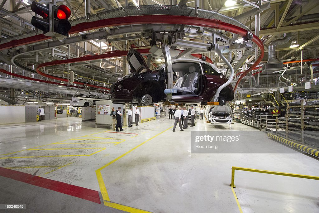 An Adam Opel AG automobile moves along an overhead conveyor at the Opel factory, operated by General Motors Co. (GM), in Eisenach, Germany, on Wednesday, April 23, 2014. European sales at Opel and its U.K. sister brand Vauxhall gained 8.5 percent to 226,888 cars in the first quarter, slightly better than the 8.1 percent increase for the market overall, according to ACEA data. Photographer: Martin Leissl/Bloomberg via Getty Images