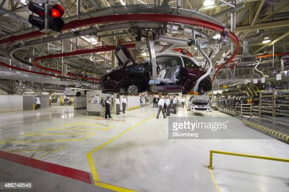 An Adam Opel AG automobile moves along an overhead conveyor at the Opel factory operated by General Motors Co in Eisenach Germany on Wednesday April...