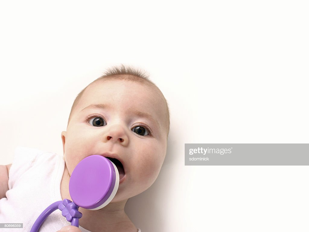 An adorable 4 month old teething baby trying to bite a rattle. : Stock Photo