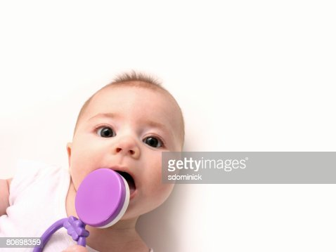 An adorable 4 month old teething baby trying to bite a rattle.