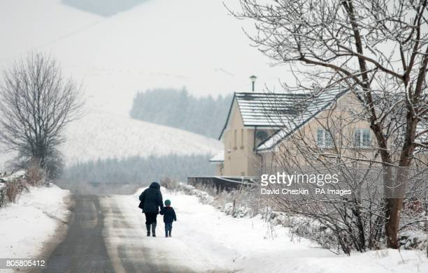 An adult and child walk down a country road as snow showers return to the Scottish BordersPicture date Thursday January 14 2010 See PA story WEATHER...