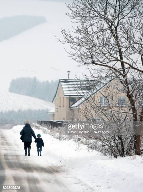 An adult and child walk down a country road as snow showers return to the Scottish Borders