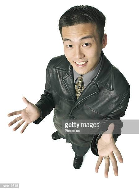 an adult asian business man in a leather jacket gestures with his hands and smiles up at the camera