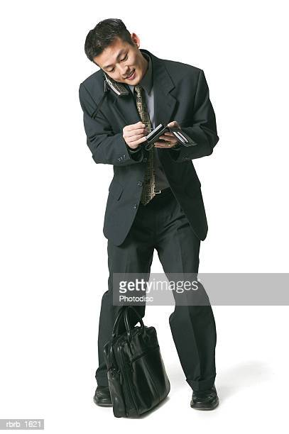 an adult asian business man in a suit talks on his phone and uses his palm pilot