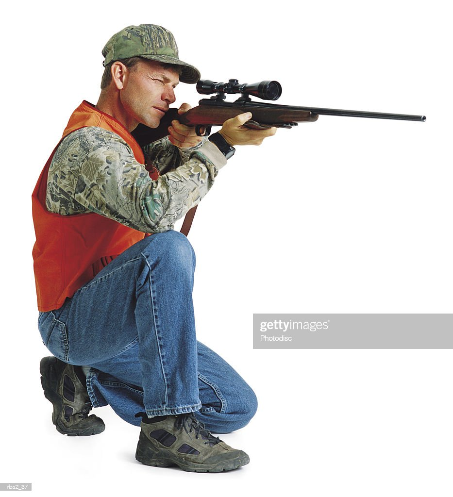 an adult caucasian male hunter in camouflage and an orange vest kneels down and holds up his rifle to line up a shot