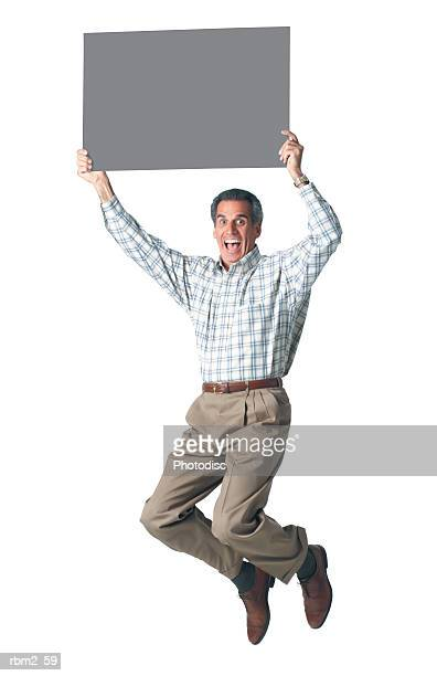 an adult caucasian man in tan pants and plaid shirt jumps into the air holding a sign up above his head