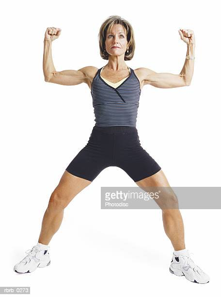 an adult caucasian woman is wearing black and gray as she stands with legs apart and arms up showing her muscles