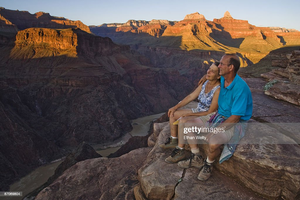 An adult couple sit together looking down at the Colorado River from Plateau Point, Grand Canyon National Park, Arizona.
