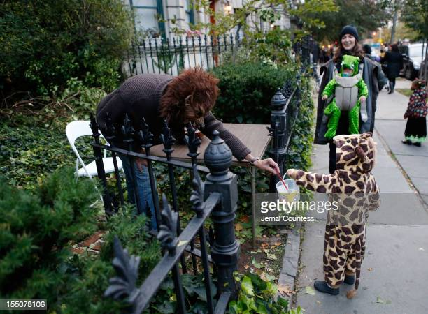 An adult dressed as a werewolf gives candy to a young child who is 'trick ot treating' as Brooklyn residents participate in Halloween activities on...