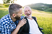 An adult hipster son with his senior father in wheelchair on a walk on a meadow in nature at sunset, laughing. Close up.