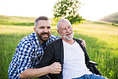 An adult hipster son with his senior father in wheelchair on a walk on a meadow in nature at sunset, laughing.