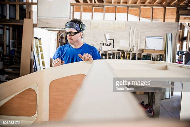 An adult, male carpenter working in his wood shop