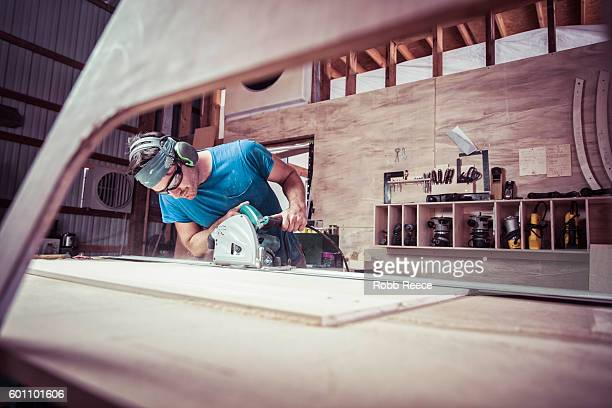 An adult, male carpenter working with power tools in his wood shop