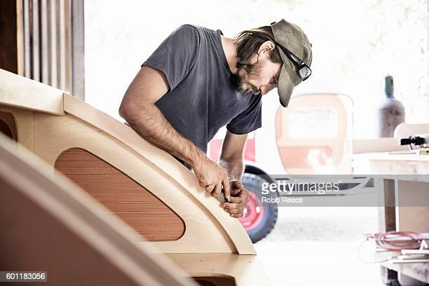 An adult, male carpenter working with tools in his wood shop